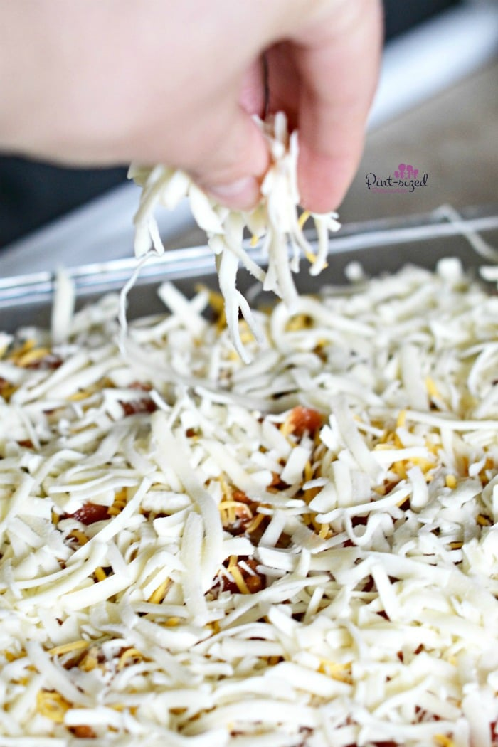 Creating the easy taco bake with layers of shredded cheese.