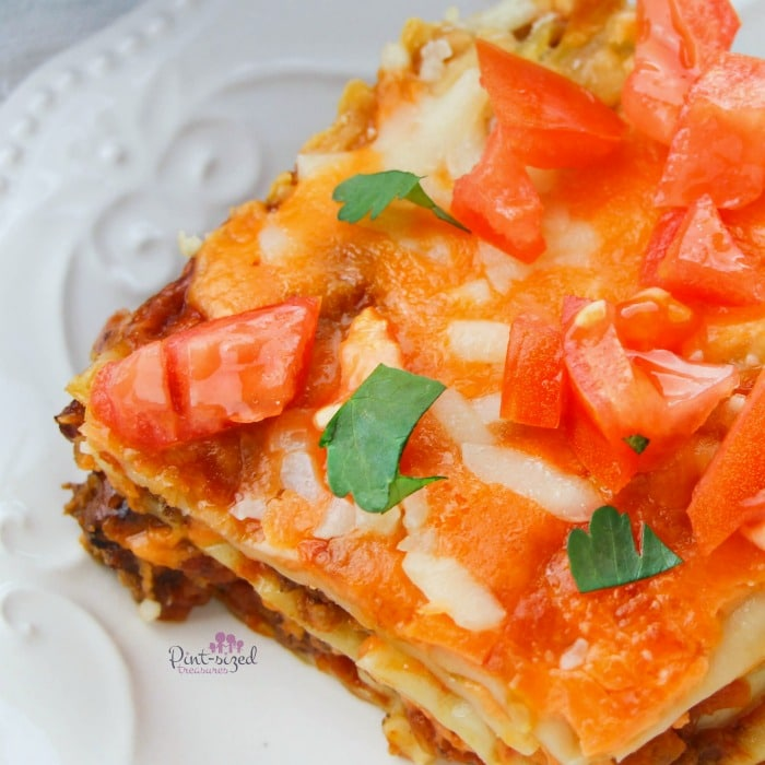 Easy taco lasagna all dressed up with fresh cilantro and diced tomatoes