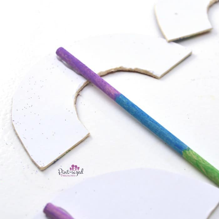 attaching the wand to the paper rainbow