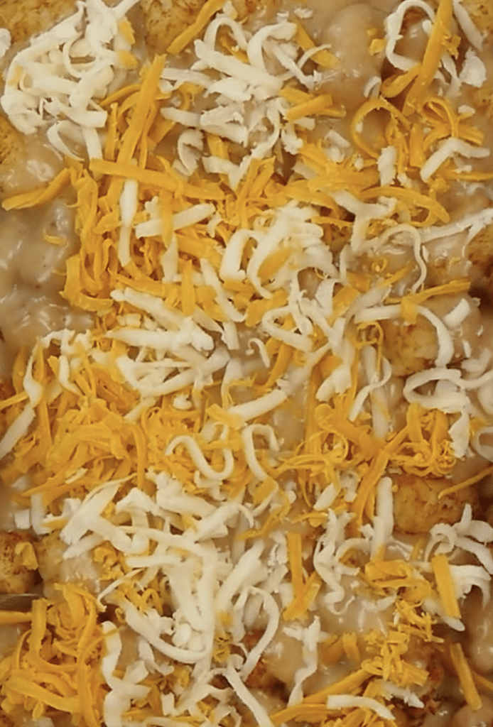pouring cheese over tater tot casserole