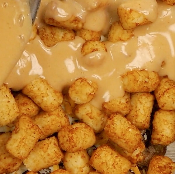 pouring mixture over tater tots for casserole
