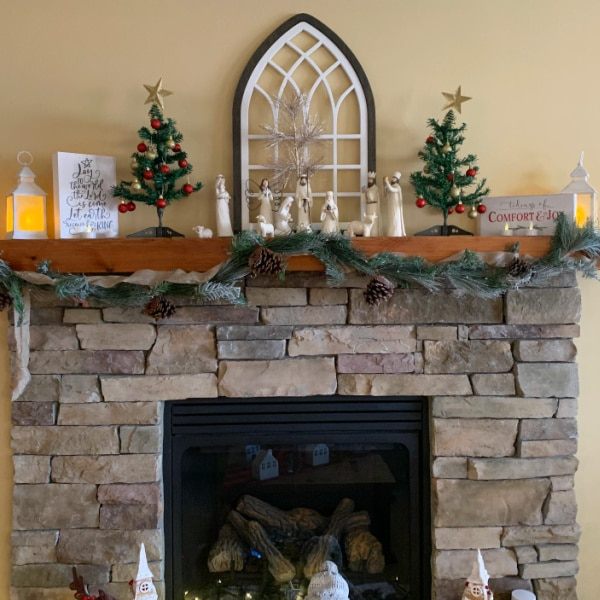 mantel with garland before cleaning and organizing