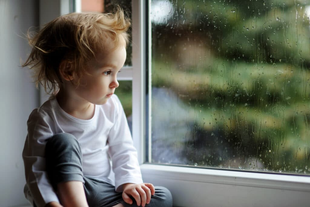 cranky toddler sitting by window