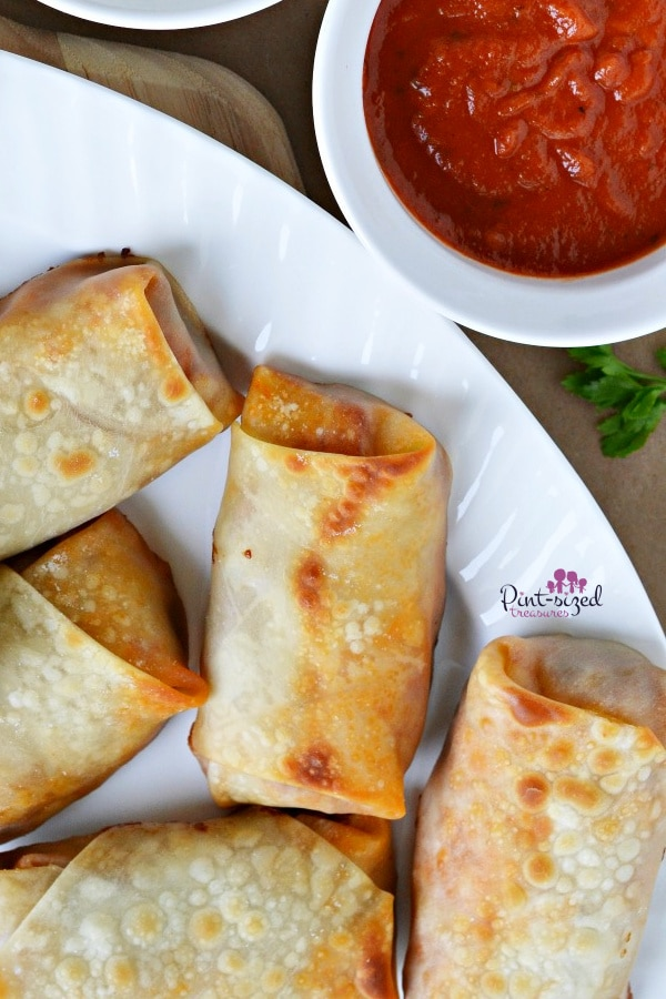 pizza egg rolls with dipping sauces on tray