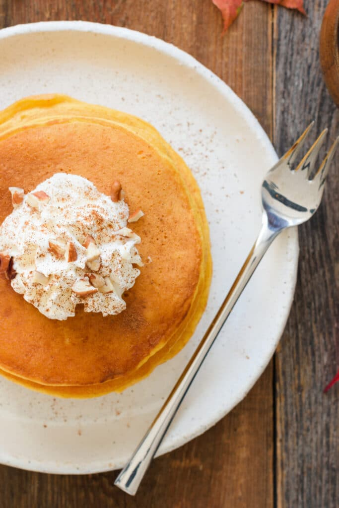 pumpkin pancakes with whipped cream on white plate