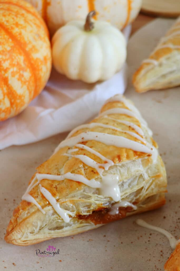 pumpkin turnovers on white parchment paper with sprinkles of cinnamon